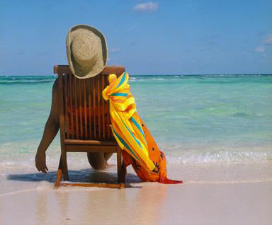 lounging on a wooden chair on a white sand beach