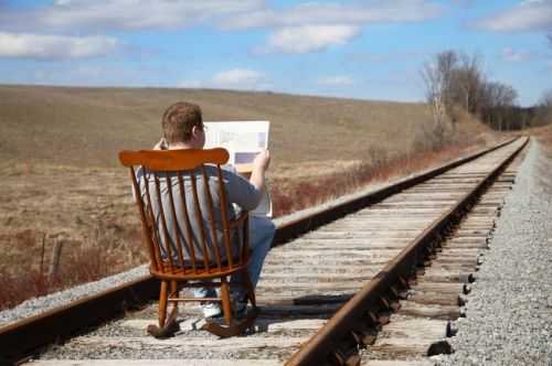 man reading paper on railroad