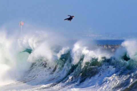a surfer flies off of a wave