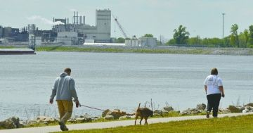 people walking a dog with industrial background