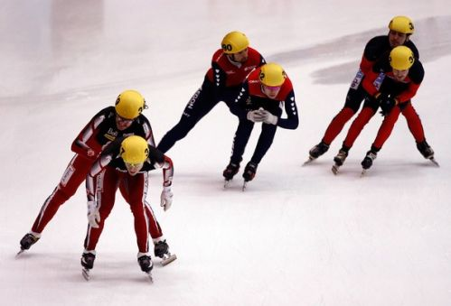 speed skaters touch eachother